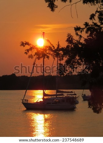 Silhouette of a sailboat at sunset on a lake - stock photo