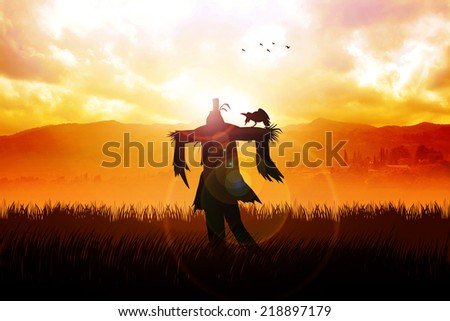 Silhouette of a scarecrow on a field - stock photo