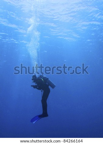 Silhouette of a scuba diver in the water in a upright position breathing air - stock photo