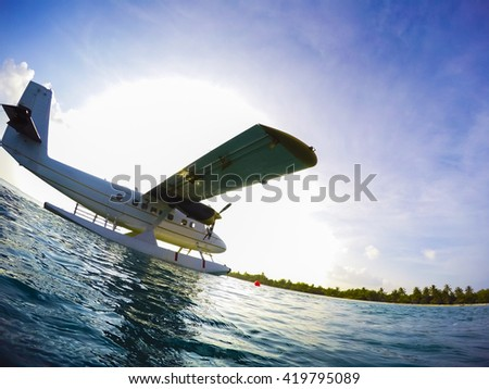 silhouette of a sea plane against strong light - stock photo