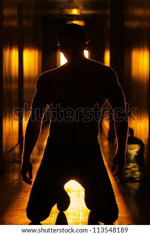 Silhouette of a sexy mysterious man with good body in glowing retro hallway - stock photo