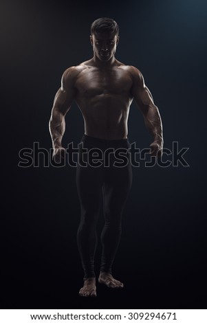 Silhouette of a shirtless strong bodybuilder preparing for training. Dramatic concept photo of confident young fitness man with core muscles, power hands and clenched fists. - stock photo
