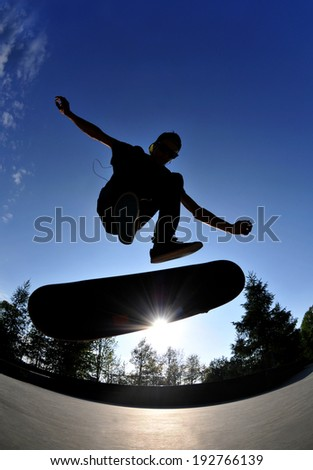 Silhouette of a skateboarder doing a flip trick at the skate park.  - stock photo