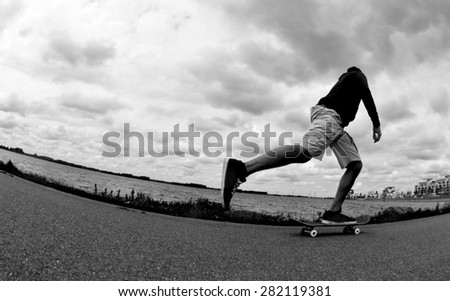 Silhouette of a skateboarder pushing around - stock photo