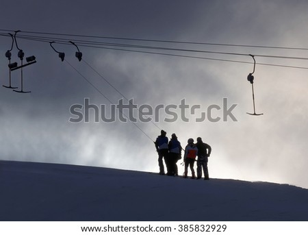 Silhouette of a ski lift and and skiers in evening light - stock photo