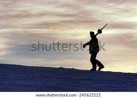 Silhouette of a skier climbing . - stock photo