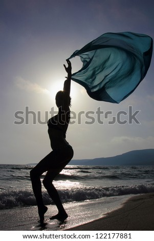 silhouette of a slim girl playing with a veil in a windy beach - stock photo