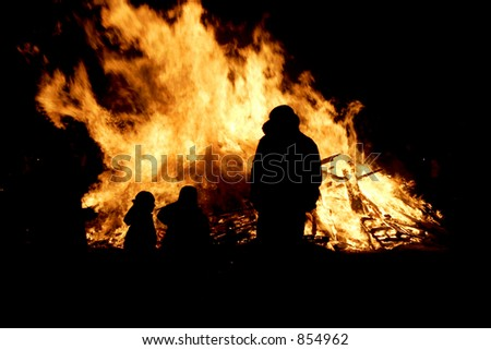 silhouette, of a small family in front of a bonfire