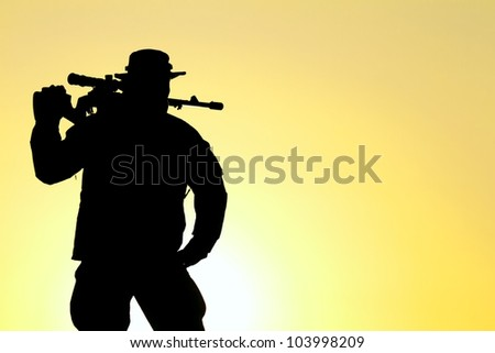 silhouette of a soldier with a background yellow sunset - stock photo