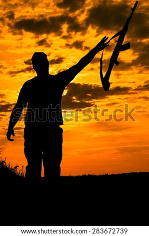 silhouette of a soldier with a gun  - stock photo