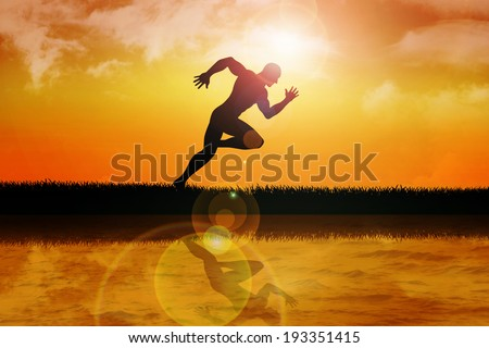 Silhouette of a sprinter at sunset - stock photo