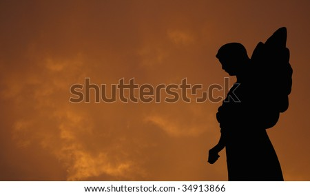 Silhouette of a Statue of an Angel with Storm Clouds