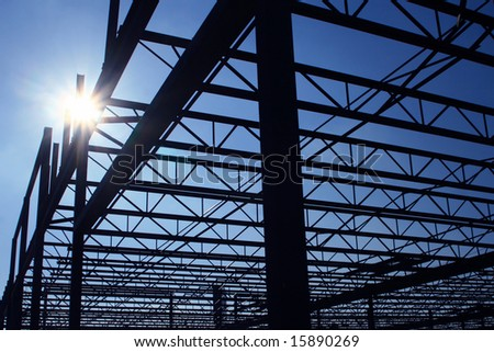 Silhouette of a steel frame building under construction.
