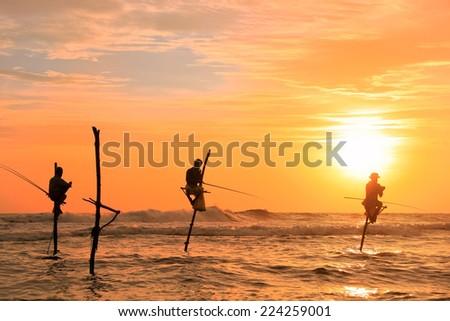 Silhouette of a stick fishermen at sunset, Unawatuna, Sri Lanka - stock photo