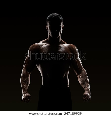 Silhouette of a strong fighter. Confident young fitness man with strong hands and clenched fists.  - stock photo