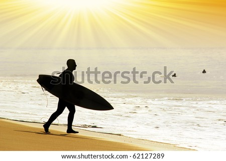 Silhouette of a surfer entering in the sea to catch some waves - stock photo