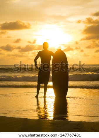 SIlhouette of a Surfer on the beach in Thailand - stock photo