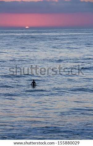 Silhouette of a surfer watching the sunset while waiting for a wave.