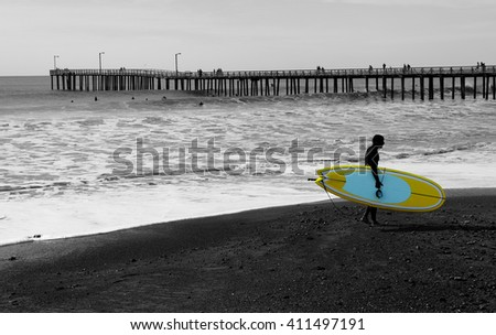 Silhouette of a surfer who carries his board at sunset on the background of a pier. - stock photo