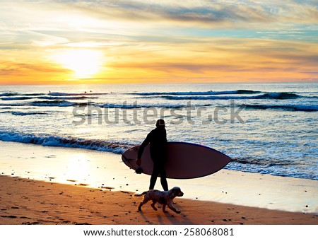 Silhouette of a surfer with a dog walking at sunset on the beach - stock photo