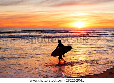 Silhouette of a surfer with surfboard on the beach at sunset. Portugal - stock photo