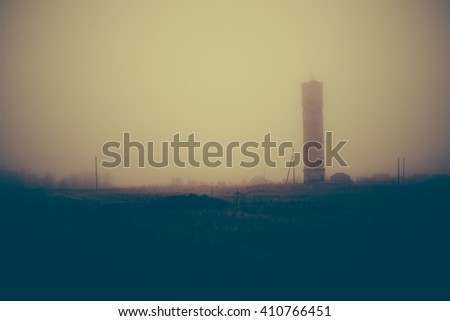 Silhouette of a tower in the fog. Evening photo.