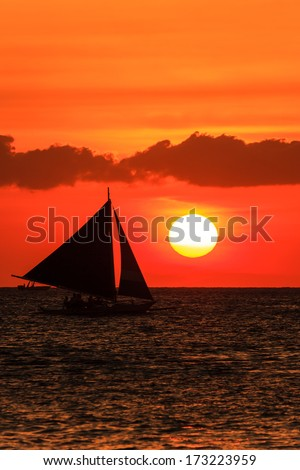 Silhouette of a traditional banca boat against a red sky and tropical sunset - stock photo