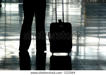 Silhouette Of A Traveler In An Airport With Their Carry On Luggage - stock photo
