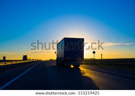 Silhouette of a truck on road at sunset - stock photo