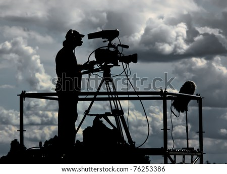 Silhouette of a TV cameraman against a cloudy sky - stock photo