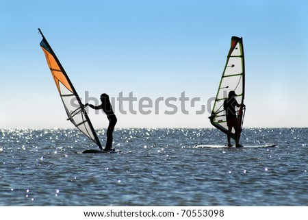 Silhouette of a two windsurfers on the sea - stock photo