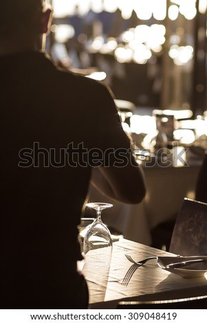silhouette of a waiter serve banquet tables at outdoor restaurant - stock photo