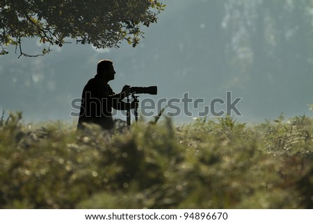Silhouette of a wildlife photographer in an outdoor park in winter. - stock photo