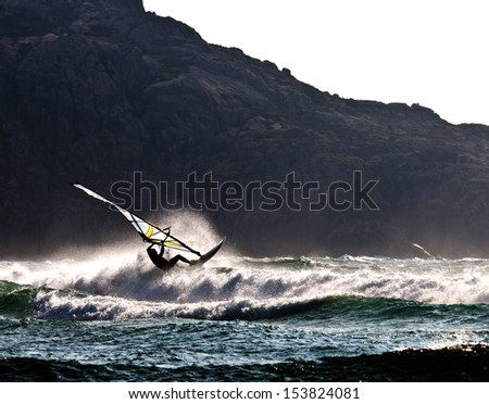 Silhouette of a wind surfer against the evening light near Cabo Villan in Galicia, Spain - stock photo