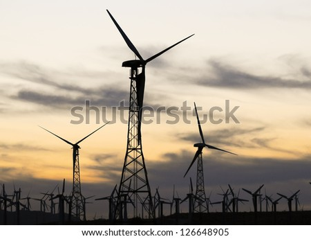 Silhouette of a wind turbine during sunset.  Palm Springs, California. - stock photo