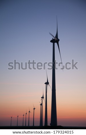 Silhouette of a Windfarm during sunset - stock photo