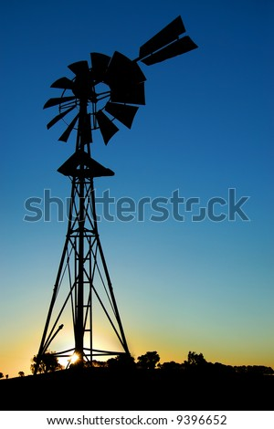 Silhouette of a windmill at sunset - stock photo