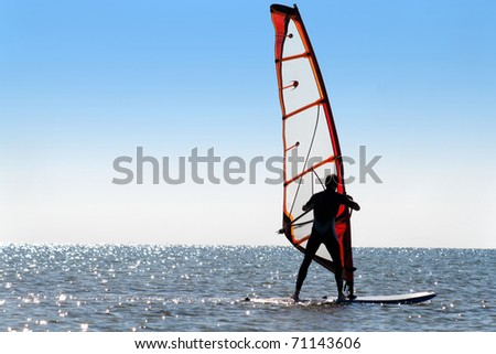 Silhouette of a windsurfer on the sea - stock photo