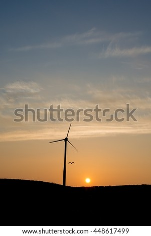 Silhouette of a windturbine with bird at sunrise.