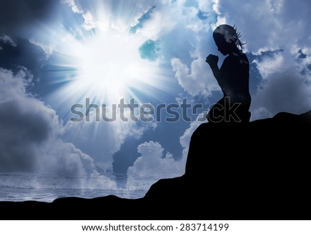 silhouette of a woman alone with God  - stock photo