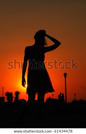 Silhouette of a woman at sunset - stock photo