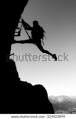 Silhouette of a woman climbing steep vertical wall - stock photo