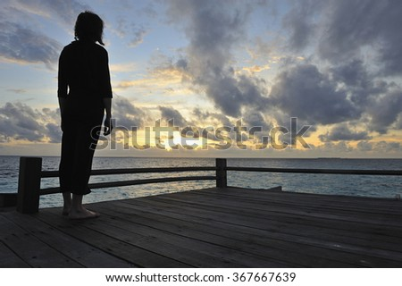 Silhouette of a woman contemplating the sunrise, Island of Borneo, Sabah State, Malaysia - stock photo