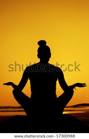 Silhouette of a woman doing yoga/meditation pose at sunset on the beach. - stock photo