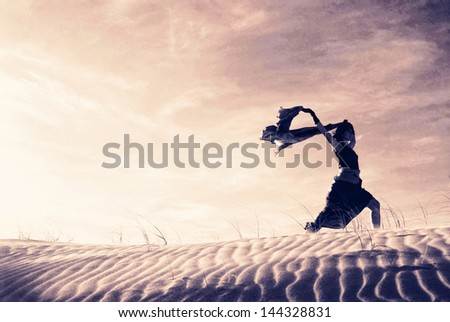 Silhouette of a woman holding a blowing scarf in the dunes. - stock photo