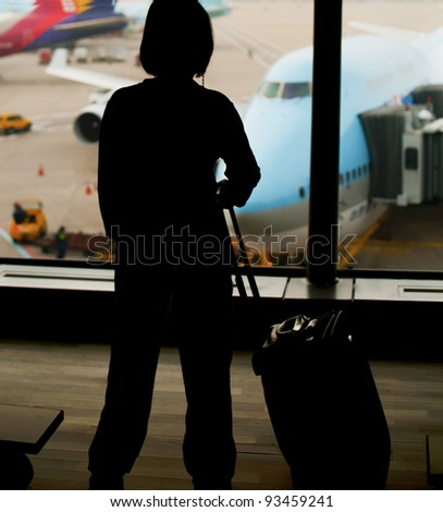 Silhouette of a woman in a airport looking at the airplane - stock photo