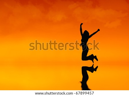 Silhouette of a woman jumping at sunset
