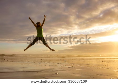 Silhouette of a woman jumping  on a the beach at the sunset