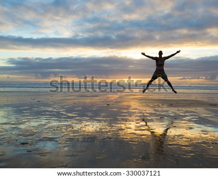Silhouette of a woman jumping  on a the beach at the sunset - stock photo