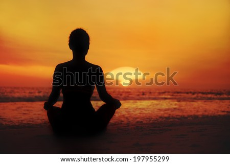 silhouette of a woman looking at sunset on the sea